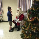 This is Santa (Wor. Ron Jackson) seeing his first child to receive his wish list.